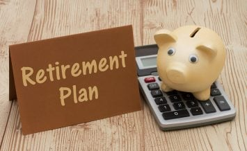 Having a retirement plan A golden piggy bank card and calculator on wood background with text Retirement Plan