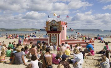 WEYMOUTH, DORSET, ENGLAND - AUGUST 31: Holiday makers sitting on the sands of Weymouth beach to watch a traditional Punch and Judy show on August 31 2012.  The old fashioned performance is attracting more tourists to the area.