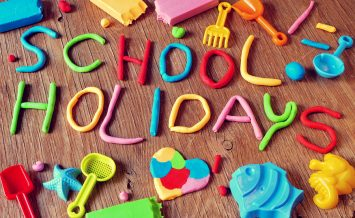 the text school holidays made from modelling clay of different colors and some beach toys such as toy shovels and sand moulds, on a rustic wooden surface