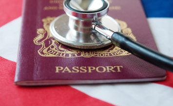 Concept photo for health issues in United Kingdom.  Passport and stethoscope on flag.