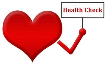 Red heart holding a signboard in hand with health check text in it.