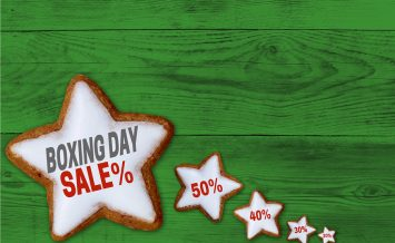 Boxing Day Sale cinnamon star on green wood concept.