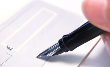 Signing a blank cheque with a fountain pen ** Note: Shallow depth of field