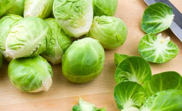 Cleaned brussel sprouts on a wooden cutting board with exterior leaves and a knife.