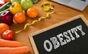 OBESITY Fitness and weight loss concept fruit and tape measure on a wooden table top view
