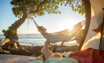an image of a couple camping in Hawaii, with one taking a picture of the other in a hammock